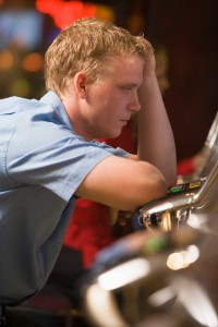 Dejected Looking Man Leaning Over A Slot Machine | Illinois Abilify Lawsuit