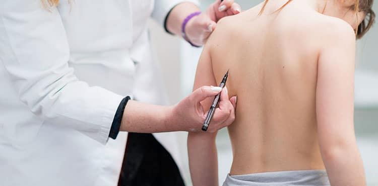 Girl being examined for Scoliosis - MAGEC Rod Spinal Implant Lawsuit