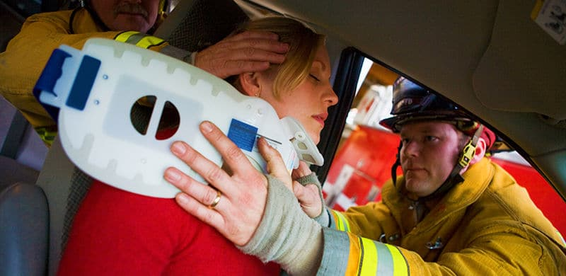 Woman being helped by firemen | Kansas Car Accident Lawyer